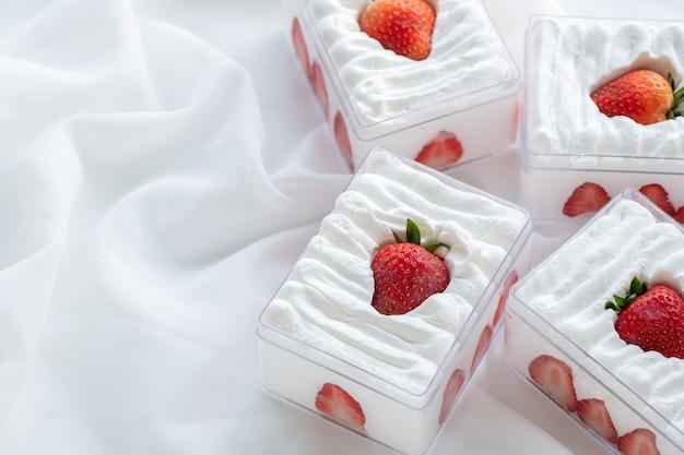 Sablé aux fraises dans une boîte en plastique sur fond de tissu et espace de copie, concept minimal de gâteau et de boulangerie