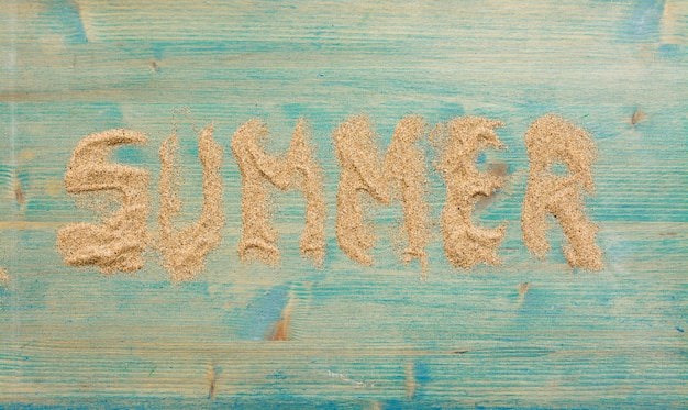 Sable sur bois bleu avec le mot summer.