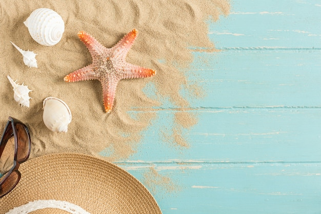 Sable et coquillages sur le plancher en bois du bleu, concept d'été