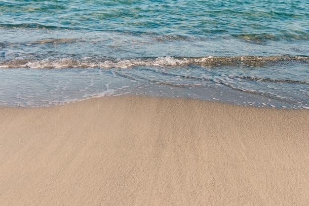 Sable fin à la plage et eau de mer claire