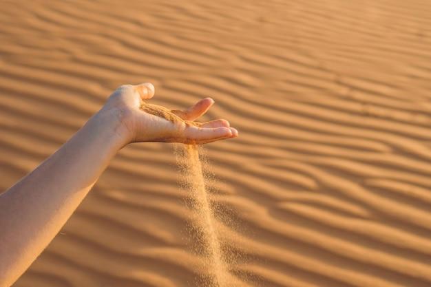 Le sable glissant entre les doigts d'une main de femme dans le désert