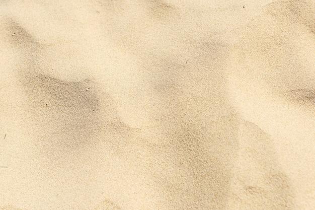 Sable jaune naturel sur le fond de la plage
