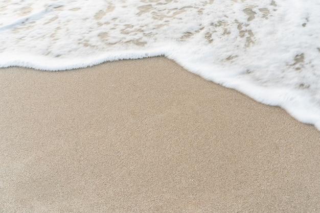 Sable lisse à la plage et belle vague en scène.