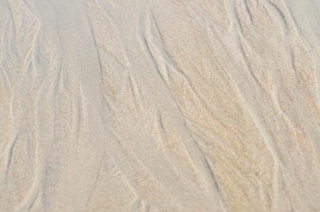 Le sable le long de la mer est un arrière-plan flou à motifs.