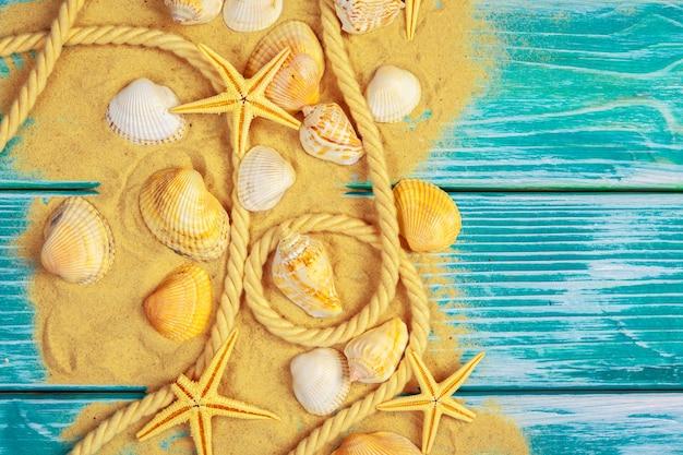 Sable de mer et coquillages sur plancher de bois bleu
