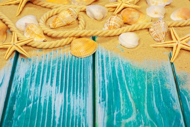 Sable de mer et coquillages sur plancher en bois bleu