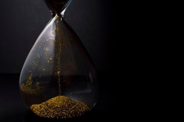 Sable et paillettes dorées passant à travers les ampoules de verre d'un sablier mesurant la passe