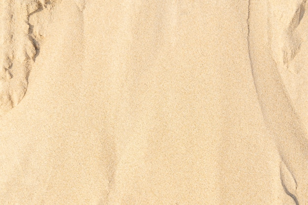 Sable sur la plage en arrière-plan. modèle de texture de sable de mer beige clair, fond de texture de plage de sable.