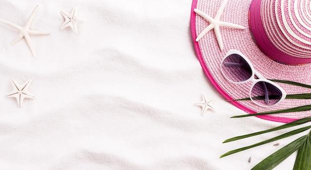Sable de plage avec coquillages, feuilles de coco, chapeau de plage et étoile de mer