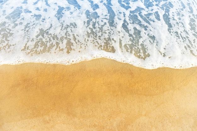 Le sable de plage et l'océan ou la vague de mer bleue avec de la mousse, peuvent être utilisés pour le fond marin