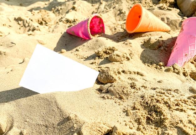 Sur le sable se trouve une carte de visite blanche sur le fond de jouets pour enfants