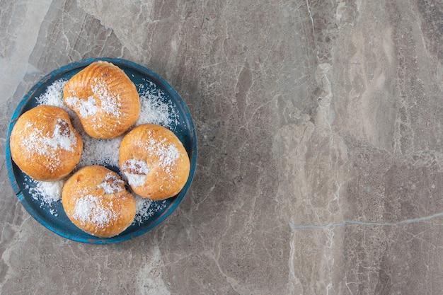 Sablés au miel avec flocons de noix de coco sur une plaque en bois sur marbre.