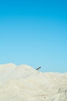 Sables blancs, ciel bleu et tuyau rouillé
