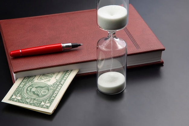 Sablier, argent, stylo et cahier sont sur la table. articles de bureau d'affaires