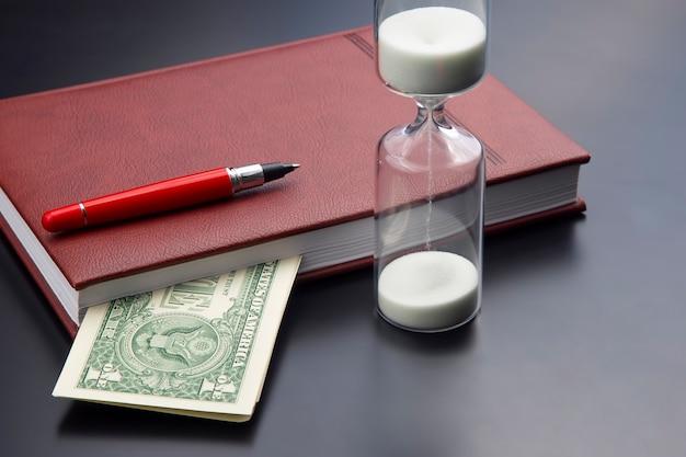 Sablier, argent, stylo et cahier sont sur la table.