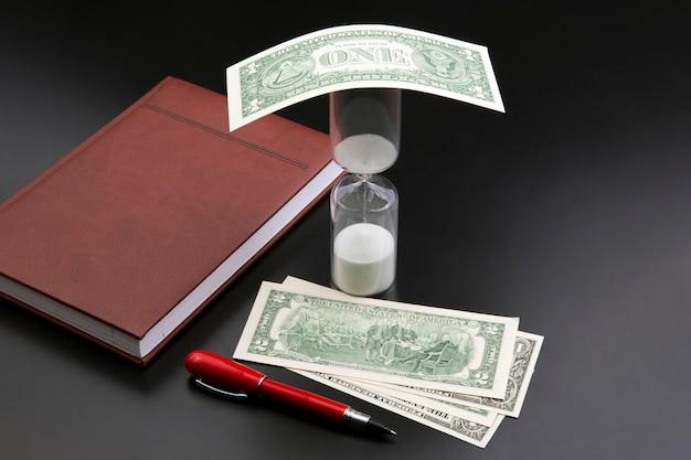 Sablier, argent, stylo et cahier sont sur la table