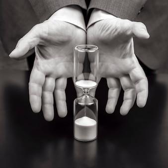 Sablier à côté des mains d'un homme d'affaires. temps de travail. planification des objectifs de réussite