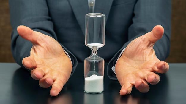 Sablier à côté des mains d'un homme d'affaires.