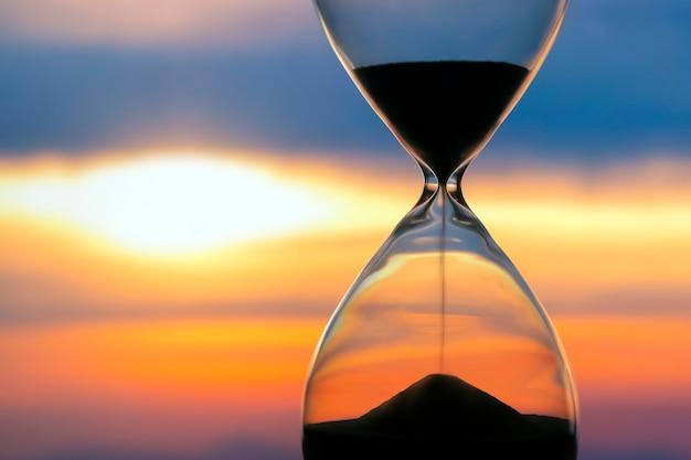 Sablier sur un coucher de soleil. la valeur du temps dans la vie. une éternité.