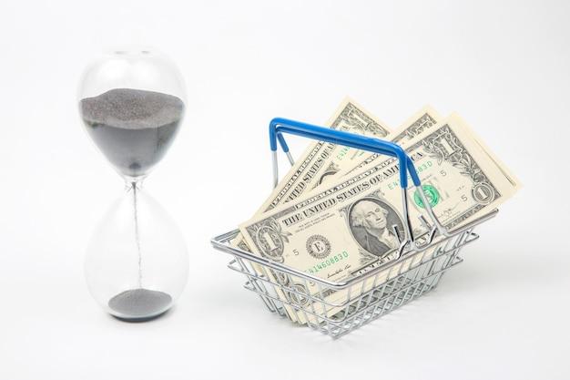 Sablier et dollars dans un panier de supermarché. acheter de la nourriture et des biens. entreprise à vendre. enregistrer des achats