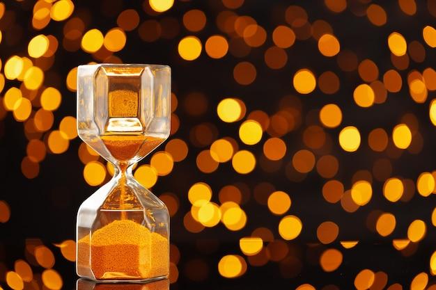 Sablier doré contre les lumières dorées du bokeh