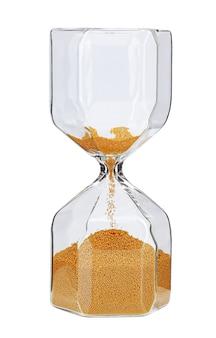 Sablier avec du sable doré sur une surface blanche