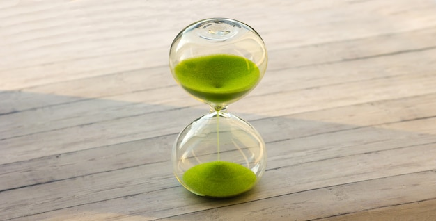 Sablier avec du sable vert sur un fond en bois