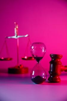 Sablier, écailles et marteau de juge en bois en néon rose. image verticale.
