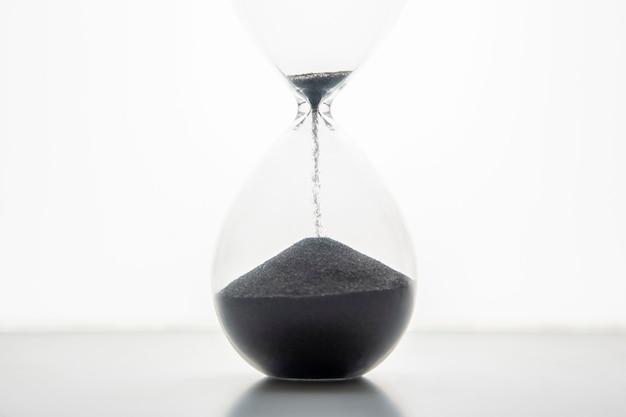 Sablier sur fond clair. le temps, c'est de l'argent. solutions d'affaires dans le temps.