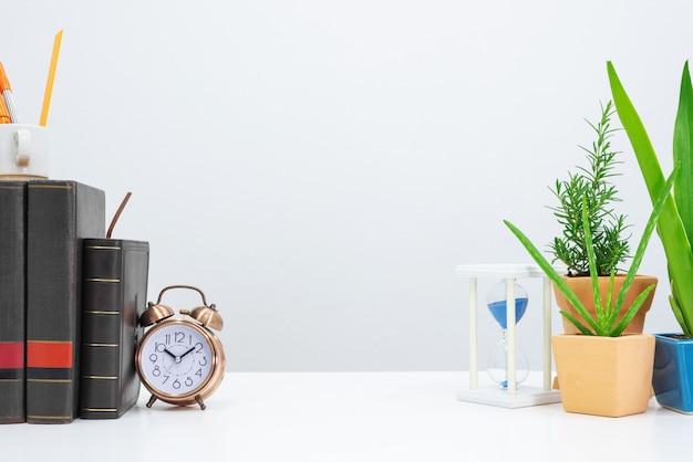 Sablier, livre, horloge, agave, aloe vera et livre sur table de bureau.