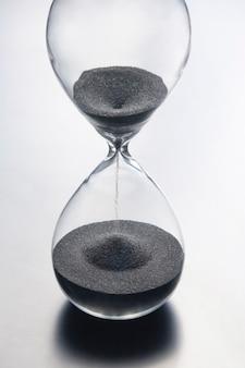 Sablier sur une lumière. le temps, c'est de l'argent. solutions d'affaires dans le temps.