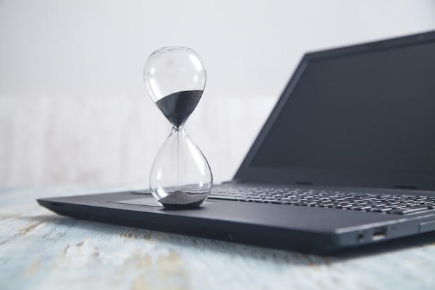 Sablier et ordinateur portable sur le bureau. temps. entreprise