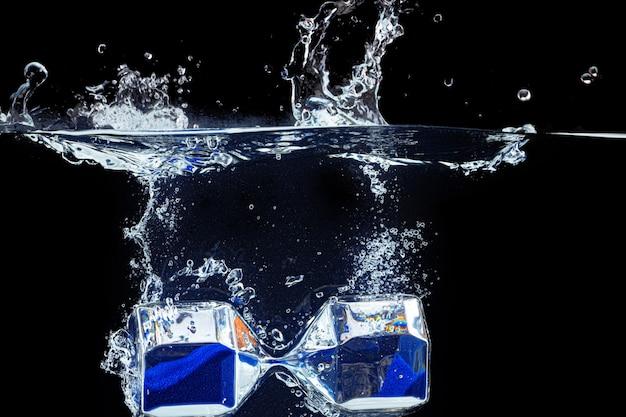 Sablier plonger dans l'eau avec une éclaboussure sur fond noir