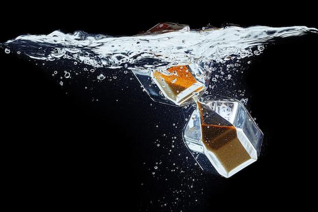 Sablier plonger dans l'eau sur fond noir