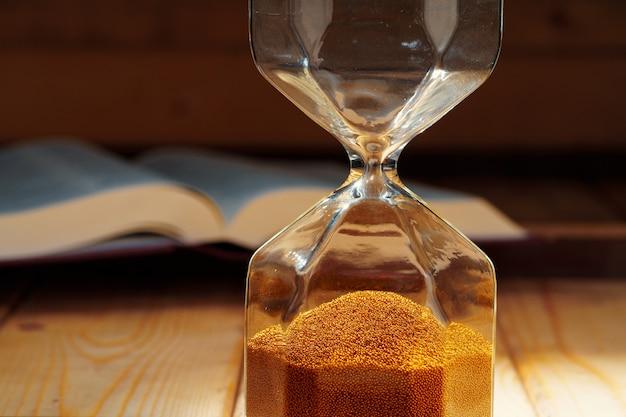 Sablier de sable doré gros plan sur la table de travail