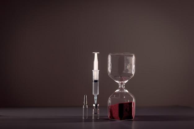 Sablier une seringue coincée dans une ampoule avec un médicament à côté de laquelle il y a une ampoule entière avec un médicament. concept de santé.