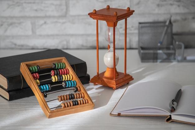 Sablier et un stylo sur une table en bois blanc avec une ombre. abacus et cahier en arrière-plan.