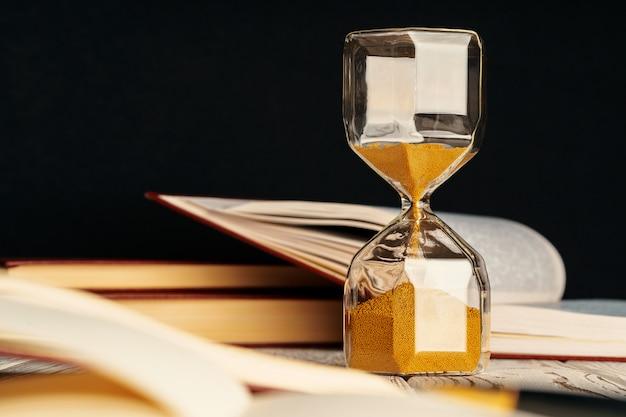Sablier sur table en bois avec livre ouvert bouchent
