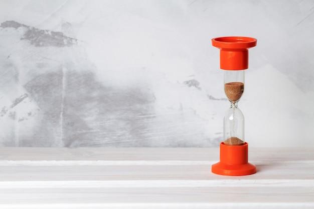 Sablier en verre sur fond de mur en béton. copier l'espace