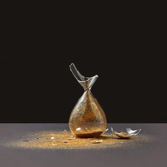 Sablier vieilli à l'ancienne s'est écrasé verticalement avec des morceaux de verre et de sable doré sur un mur sombre bicolore, copiez l'espace.