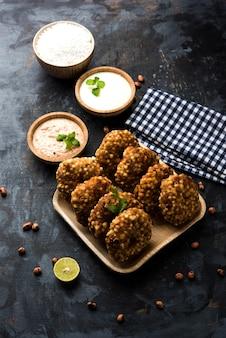 Sabudana vada ou gâteau frit au sagou servi avec un chutney d'arachide sur fond de mauvaise humeur, recette de jeûne populaire d'inde.