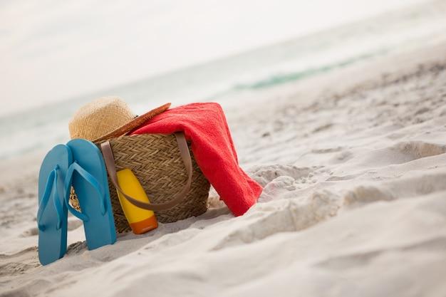 Sac avec accessoires de plage gardé sur le sable