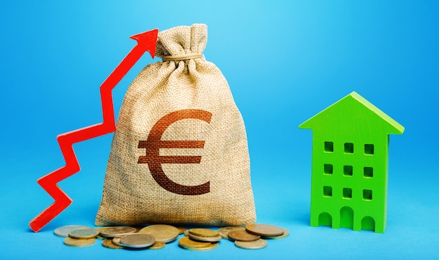 Sac d'argent en euros avec flèche rouge vers le haut et immeuble résidentiel. retour sur investissement