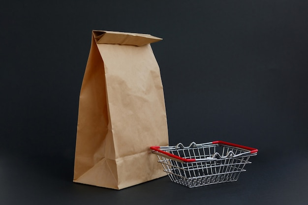 Sac artisanal en papier brun pour faire du shopping sur fond noir et un petit panier d'épicerie
