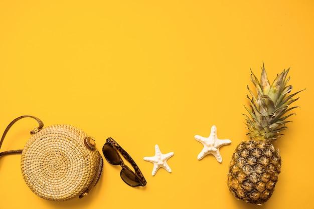 Sac en bambou, lunettes de soleil, ananas et étoile de mer sur jaune