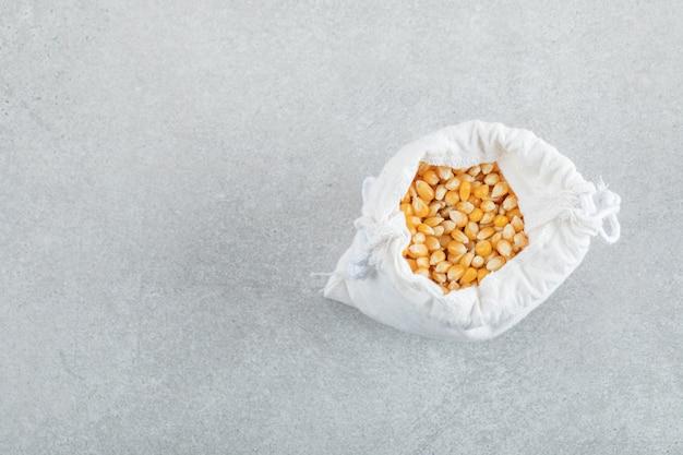 Un sac blanc plein de grains de maïs sur fond gris.