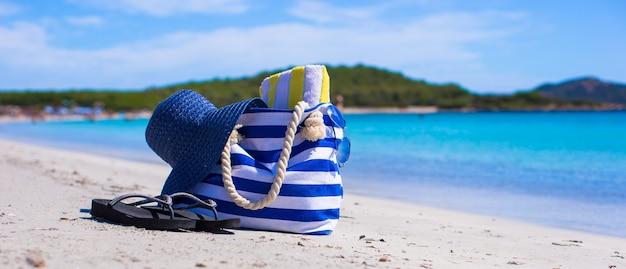 Sac bleu, chapeau de paille, des tongs et une serviette sur une plage tropicale blanche