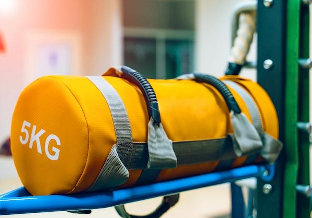 Sac de boxe jaune de cinq kilogrammes sur un support dans un gymnase.