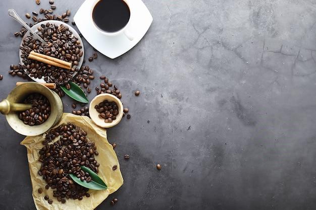 Sac de café. grains de café torréfiés sur la table. grains de café avec des feuilles vertes pour la cuisson.