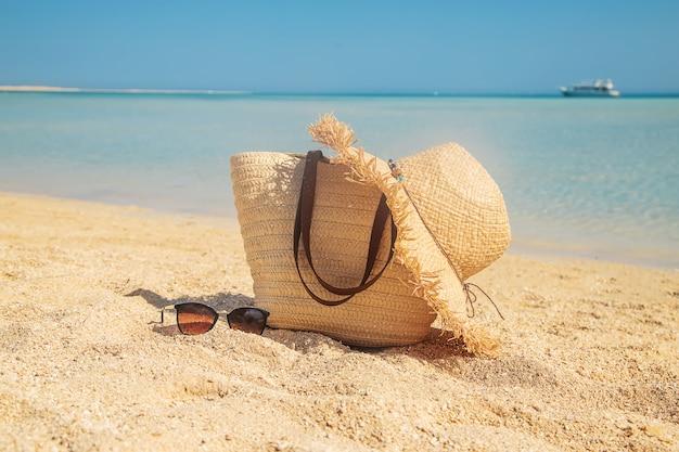 Sac et chapeau sur la plage près de la mer.